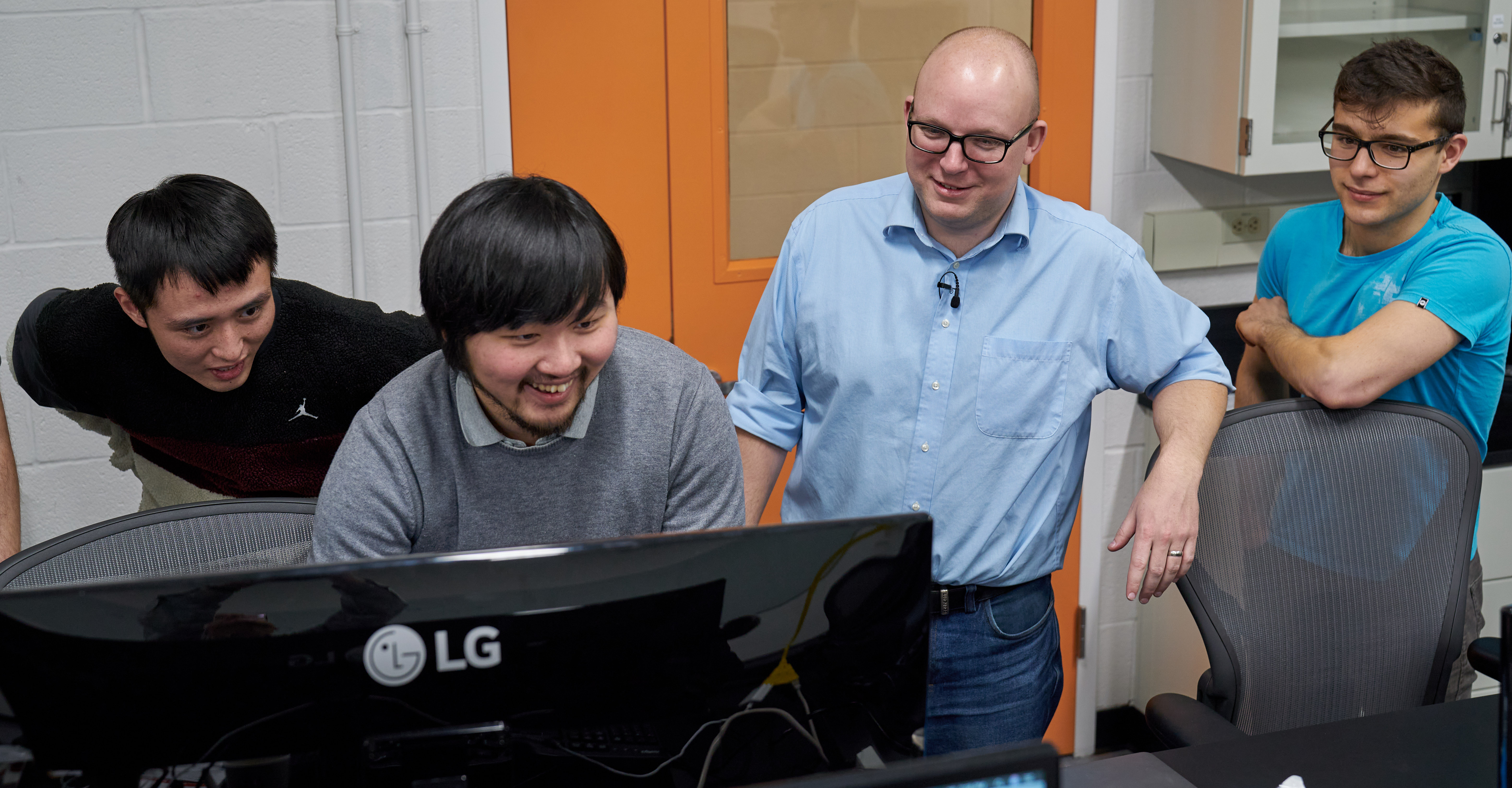 lab members and peter mcmahon gather around a computer laughing